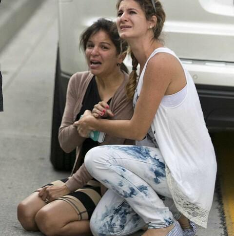 REAKSJON: Etter å ha fått liv i gutten bryter Pamela Raseo sammen i gråt mens hun blir trøstet av Lucila Gody som tilfeldigvis kom kjørende forbi. Foto: Al Diaz/Miami Herald/AP