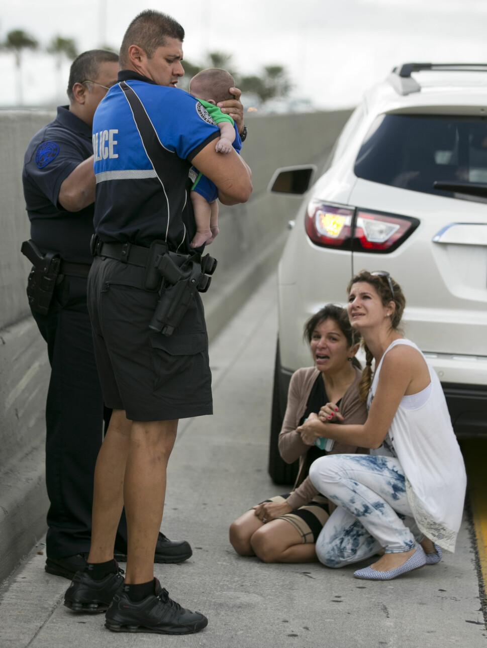 DRAMA LANGS MOTORVEIEN: Her holder politibetjent Amauris Bastidas den lille gutten mens de venter på ambulansen. På bakken sitter en gråtende Pamela og får trøst av Lucila. Foto: Al Diaz/Miami Herald/AP