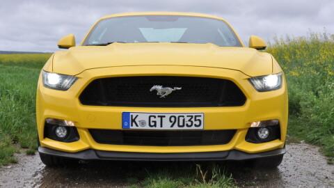Gul Mustang under mørke skyer.