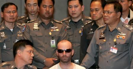 Pedofilimistenkte Christopher Paul Neil omringet av thailandsk politi under en pressekonferanse i Bangkok 19. oktober 2007. (Foto: PORNCHAI KITTIWONGSAKUL, ©pk/AD)