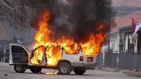 En FN-bil satt i brann under opptøyer i Mitrovica. (Foto: Reuters)