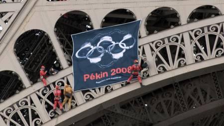 Demonstranter henger opp bannere i Eiffeltårnet. (Foto: AFP/SCANPIX)