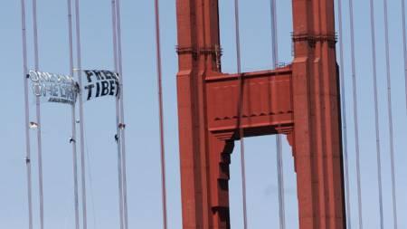 OL-fakkelen ankommer tirsdag USA og San Francisco. Allerede mandag hadde demonstrantene hengt opp bannere på Golden Gate. (Foto: AFP/SCANPIX)