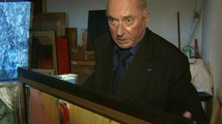 Haaken Christensen viser fram et bilde i sitt hjem i Oslo. (Foto: TV 2)