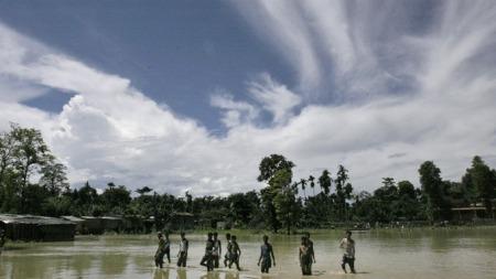 REKORD: Sesongens monsunregn i India er det tidligste på 108 år. Her vandrer landdsbybeboere Nord-Lakkhimpur gjennom den flomrammede landsbyen. (Foto: AP/SCANPIX)