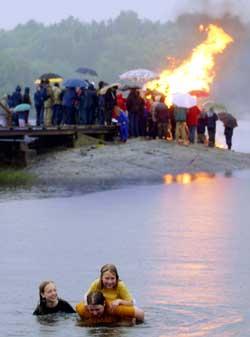 Er man først blitt våt i regnet, ja - da er det jo bare å hoppe uti med klær på... (Foto: Heiko Junge / SCANPIX)