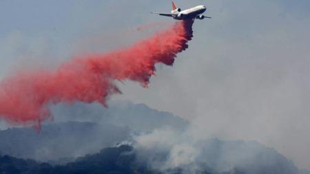 BOMBER FLAMMENE: Et DC 10-fly   bomber skogbrannen med flammedrepende kjemikalier i Green Valley i California.   (Foto: AP/SCANPIX)
