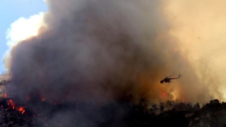 BRANNINFERNO: Helikopter bekjemper skogbrannen på fjellet Hymettus ved Papagou som er en forstad til Aten.  (Foto: AFP)