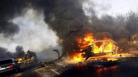 Georgisk militærkjøretøy i flammer ved Gori den 11. august.  (Foto: MARCO LONGARI/AFP)