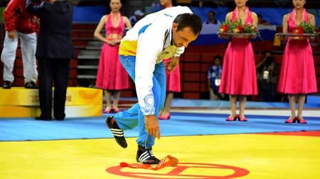 PROTEST: Her protesterer Ara Abrahamian ved å kaste OL-bronsen sin i gulvet. (Foto: Vanda Biffani/AP)