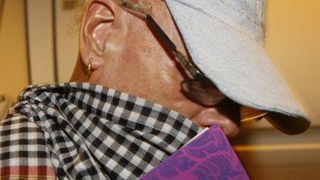 Gary Glitter forøskte å skjule ansiktet sitt da han gikk ombord på flyet fra Vietnam til Bangkok tirsdag.