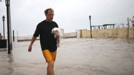 IKE TREFFER FLORIDA: Selv i dårlig vær må hunden luftes. (Foto: Carlos Barria, ©REUTERS)