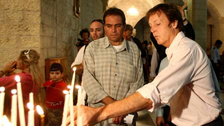 Den tidligere bassisten i the Beatles tente et lys for fred i Bethlehemskirken.  (Foto: AHMAD GHARABLI/AFP)