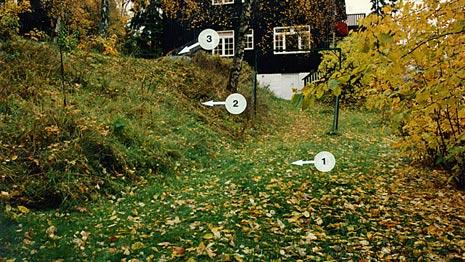 Politiets egne åstedsbilder viser hvor William Nygaard ble funnet. Pil 1 markerer funnstedet, pil 2 viser til skråningen og pil 3 til bilen