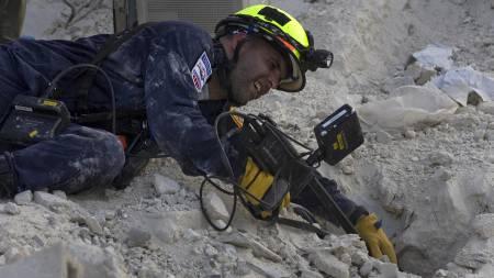 VANSKELIG REDNINGSARBEID: En brannmann leter etter overlevende i ruinene.  (Foto: Ramon Espinosa/AP / SCANPIX)
