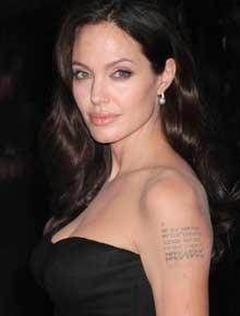 SNODIG: Av kjærlighet til sine barn har Angelina Jolie latt mindre pene tatoveringer feste seg på overarmen.