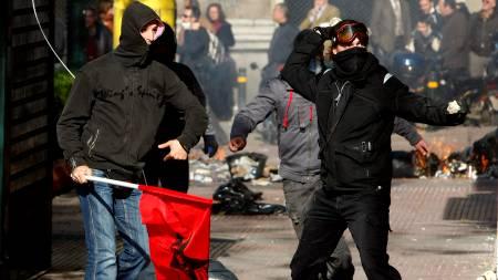 KASTER STEIN: Demonstranter kaster stein mot politiet i Aten   onsdag. Urolighetene startet lørdag da en tenåring ble skutt og drept   av politiet. (Foto: YIORGOS KARAHALIS/REUTERS)