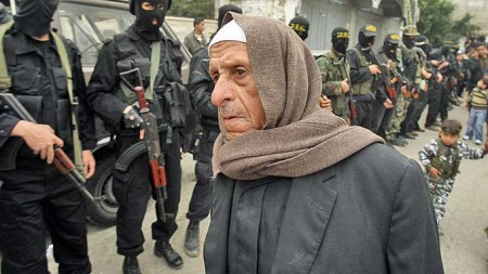 A Palestinian man walks past Islamic Jihad militants during an anti-Israel rally in Bureij refugee camp in the Southern Gaza Strip December 26, 2008 (Foto: Reuters)