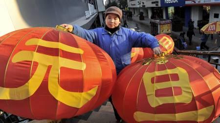 Kina forbereder deg på nyttårsfeiring. En kvinne bærer lanternene med tegnene Yuan Dan som betyr den første dagen i det nye året.  (Foto: AP/SCANPIX/)