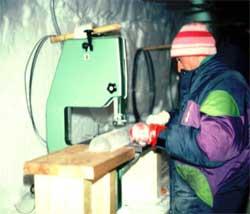 En forsker sager opp en iskjerne på Grønland. Kjernene hentes opp ved at et hult rør bores dypt ned i isen. Når røret trekkes opp ligger iskjernen med inni. (Foto: Wikimedia Commons)