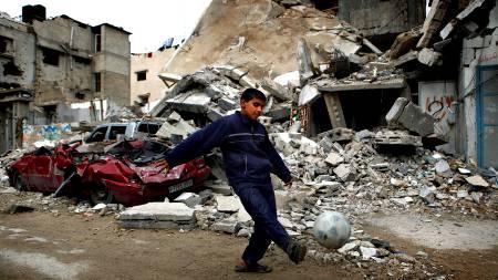 En palestinsk gutt spiller fotball foran et ødelagt hus.  (Foto: JERRY LAMPEN/REUTERS)