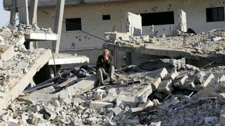 En palestiner sitter alene i runinene av et hus etter israelske luftangrep.  (Foto: SAID KHATIB/AFP)