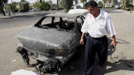 Bil ødelagt etter angrep   fra Blacwater-vakter i Bagdad. En politimann studerer vraket. (Foto:   KHALID MOHAMMED/AP)