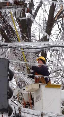 Terry Stone forsøker å fjerne isen som dekker strømledningene i Owensboro, Kentucky. (Foto: John Dunham / Scanpix)