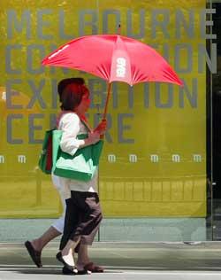 Nei, det regner ikke i Melbourne, paraplyen er for å gi skygge. Da bildet ble tatt var temperaturen 43 grader. (Foto: TIM WIMBORNE / Scanpix)
