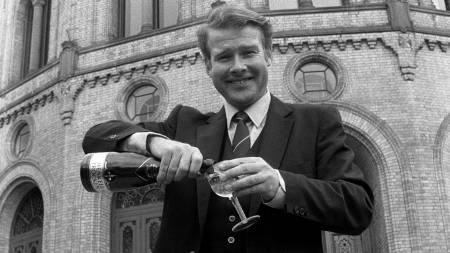 Carl I. Hagen markerer Fremskrittspartiets 10 års jubileum med en flaske sjampanje foran Stortinget. 8. april 1983.  (Foto: Knut Nedrås / NTB/SCANPIX)