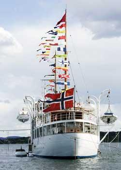 Vimplene og flagget på kongeskipet Norge løftes, men det er bare glatte bølger på sjøen. Et sted mellom svak vind og lett bris altså. (Foto: Knut Falch / Scanpix)