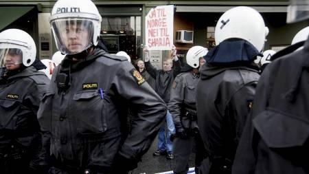 POLITIBESKYTTELSE: Leder i Norgespatriotene, Øyvind Heian, holdt en motdemonstrasjon på Egertorget i Oslo da en markering mot muslimhets i Norge passerte fredag ettermiddag. Heian måtte beskyttes av politiet.  (Foto: Lien, Kyrre/SCANPIX)