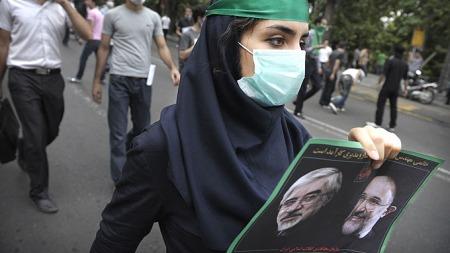 DEMONSTRERER: Tilhengere av presidentkandidat Mir Hossein Mousavi som tapte valget fredag, demonstrerer i Teherans gater. Mahmoud Ahmadinejad som vant valget blir beskyldt for valgjuks. (Foto: AFP PHOTO/OLIVIER LABAN-MATTEI)