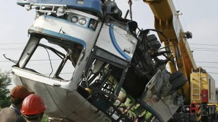 Vraket av minibussen fjernes. Minst 14 av passasjerene ble drept da minibussen ble truffet av et tog.  (Foto: Slamet Riyadi/AP)