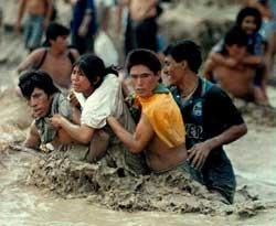 En kvinne reddes ut av vannmassene i da Nepena-elven nord for Lima gikk over sine bredder under El Nino i 1998. (Foto: Scanpix)
