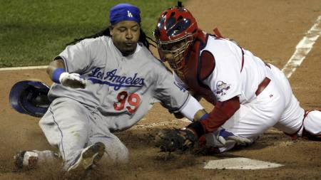 Los Angeles Dodgers' Manny   Ramirez, left, is tagged out by St. Louis Cardinals catcher Yadier Molina   on a play at home during the 12th inning of a baseball game Wednesday,   July 29, 2009, in St. Louis. Ramirez was trying to score on a single   by teammate Casey Blake. (Foto: Jeff Roberson/AP)
