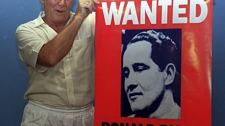 Her poserer Ronnie Biggs med en plakat før utgivelsen av hans bok: «Odd Man Out» i 1994.  (Foto: FILES/AFP)