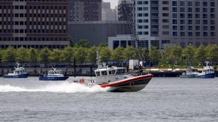 Båter fra politiet, brannvesen og kystvakten på stedet der et helikopter og et småfly havnet i elven etter å ha kollider i lufta.  (Foto: CHIP EAST/REUTERS / SCANPIX)