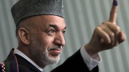 President Hamid Karzai viser fram blekket på fingeren etter å ha avgitt sin stemme ved valget.  (Foto: LUCY NICHOLSON/REUTERS)
