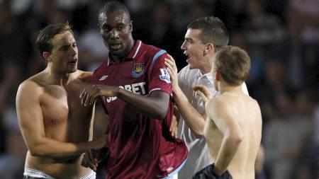 - KOM DERE VEKK: Carlton Cole ser ikke videre begeistret ut over å ha blitt omringet av tre halvnakne fans.  (Foto: STEPHEN HIRD/REUTERS)