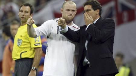 HØRER PÅ SJEFEN: Wayne Rooney får innstrukser fra Fabio Capello. (Foto: IAN KINGTON/AFP)