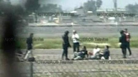 Passasjerer må sette seg på bakken utenfor flyet i påvente av   at politiet skal få kontroll på situasjonen.