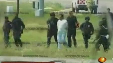 En mistenkt føres bort av soldater etter flykapringen. Lokale   medier melder at opp til åtte menn er arrestert.