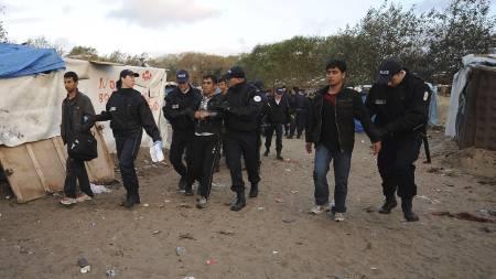 Flyktninger blir ført bort av fransk politi tirsdag morgen. (Foto: DENIS CHARLET/AFP)