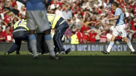 LEGGES I BAKKEN: Her legges tilskueren i bakken av sikkerhetspersonell - mens Craig Bellamy stormet mot ham. (Foto: Jon Super/AP)