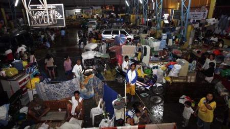 Filippinere søker tilflukt i en idrettshall omgjort til evakueringssenter i Laguna-provinsen, sør for Manila på Filippinene. (Foto: EPA/Dennis M. Sabangan)