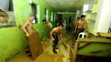 Filippinere forsøker å rydde og vaske ut gjørme av huset etter oversvømmelsene forårsaket av den tropiske stormen Ketsana. (Foto: AFP/Noel Celis)