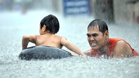 KAOS: Voksne forsøker å få sine barn i sikkerhet etter den enorme nedbørsmengden som kom i kjølevannet av den tropiske stormen Ketsana. (Foto: AFP PHOTO/JAY DIRECTO)