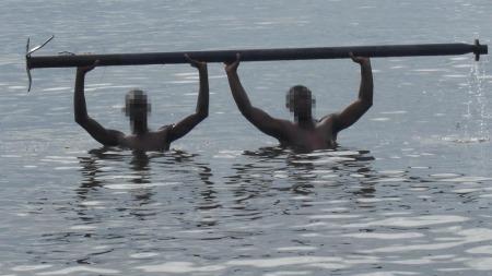 To av deltakerne på treningsleiren må holde en tung jernstang over hodet mens de står nakne i vannet på Bussi Island i Uganda.