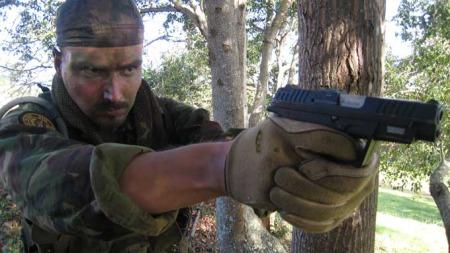 POSERER MED VÅPEN: Tjostolv Moland poserer i uniform og med våpen på Ssissi skytebane i Uganda sommeren 2008.  (Foto: Privat)
